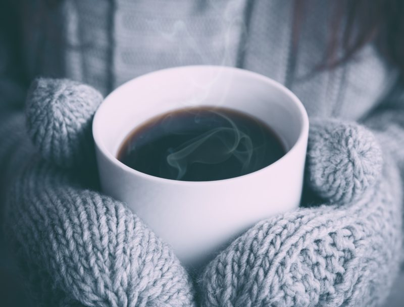 Warm mug of coffee in gloved hands